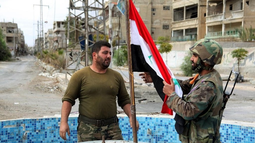 FILE - In this Friday, Nov. 8, 2013 file photo, released by the Syrian official news agency SANA, Syrian army soldiers place a national flag at a square in the Sabina suburb Syrian troops captured, south of Damascus, Syria. Two years ago, it seemed almost inevitable that President Bashar Assad would be toppled. Almost no one thinks that now. As he prepares for elections through which he is set to claim another seven-year mandate for himself, the momentum in the civil war is clearly in Assad's favor. (AP Photo/SANA, File)