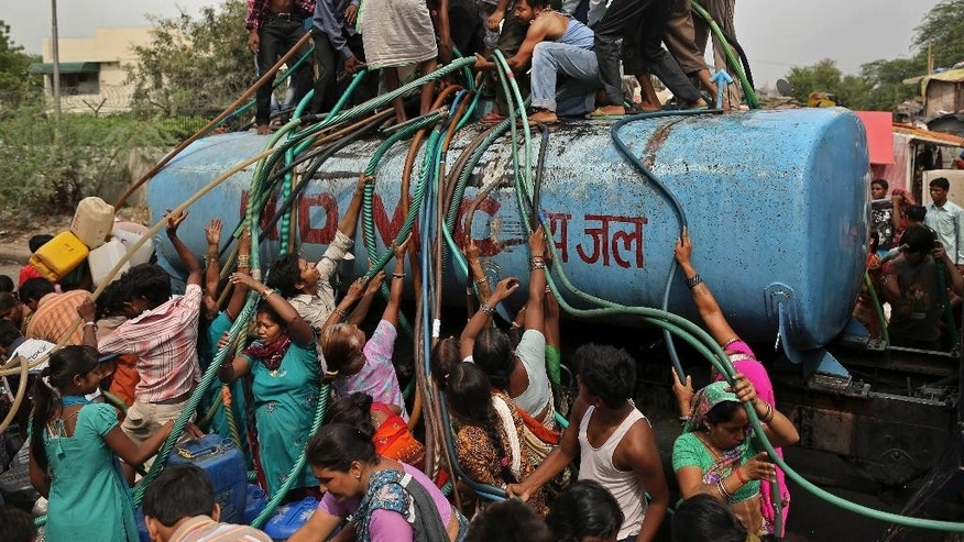 FILE - In this July 6, 2012 file photo, residents crowd around a government tanker delivering drinking water because of short supply in running water taps in New Delhi, India. As India faces certain water scarcity and ecological decline, the country's main political parties campaigning for elections have all but ignored environmental issues seen as crucial to India's vast rural majority, policy analysts say. (AP Photo/Kevin Frayer, File)