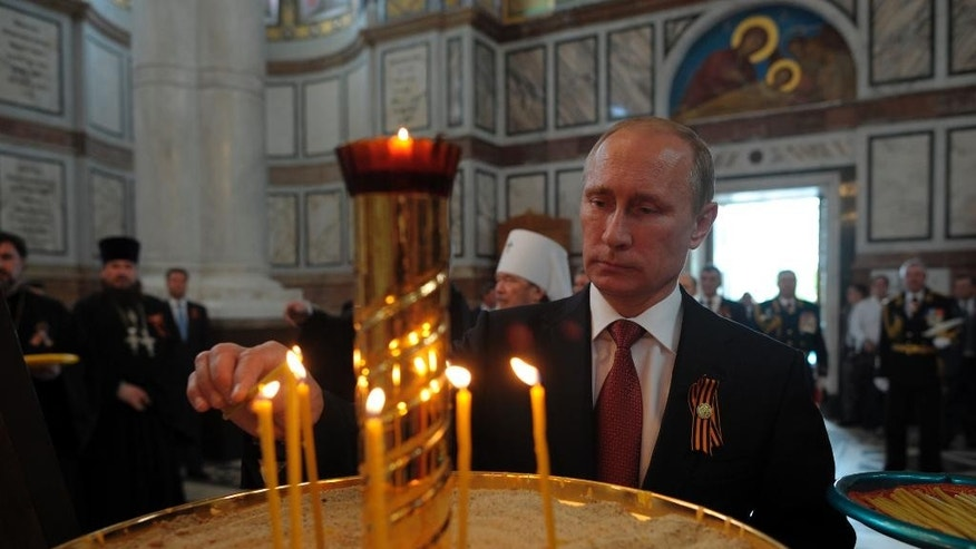 "Russian President Vladimir Putin lights a candle in Sevastopol where he attends celebrations marking  the Victory Day, in Crimea, Friday, May 9, 2014. President Vladimir Putin hailed the return of Crimea to Russia as the restoration of ""historic justice"" before a jubilant, welcoming crowd Friday on the holiday that Russians hold dearest. Putin's visit to the Crimean port of Sevastopol, was strongly criticized by both NATO and Ukraine's Foreign Ministry. (AP Photo/RIA-Novosti, Alexei Druzhinin, Presidential Press Service)"