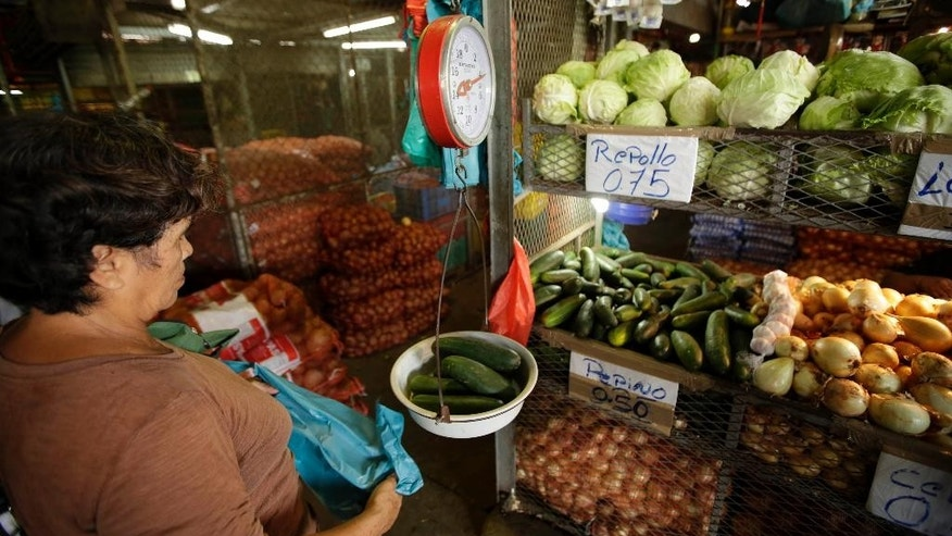 A woman weighs cucumbers on a scale at a popular market in Panama City, Thursday, May 8, 2014. The economy of this Central American country has soared during the past five years and unemployment is at a record low, but frustration with the high cost of living has been building among Panama's 3.4 million people, especially the quarter living in poverty who haven't benefited as much from the boom. (AP Photo/Arnulfo Franco)