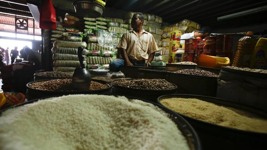 A rice salesman waits for customers at a popular market in Panama City, Thursday, May 8, 2014. The economy of this Central American country has soared during the past five years and unemployment is at a record low, but frustration with the high cost of living has been building among Panama's 3.4 million people, especially the quarter living in poverty who haven't benefited as much from the boom. (AP Photo/Arnulfo Franco)