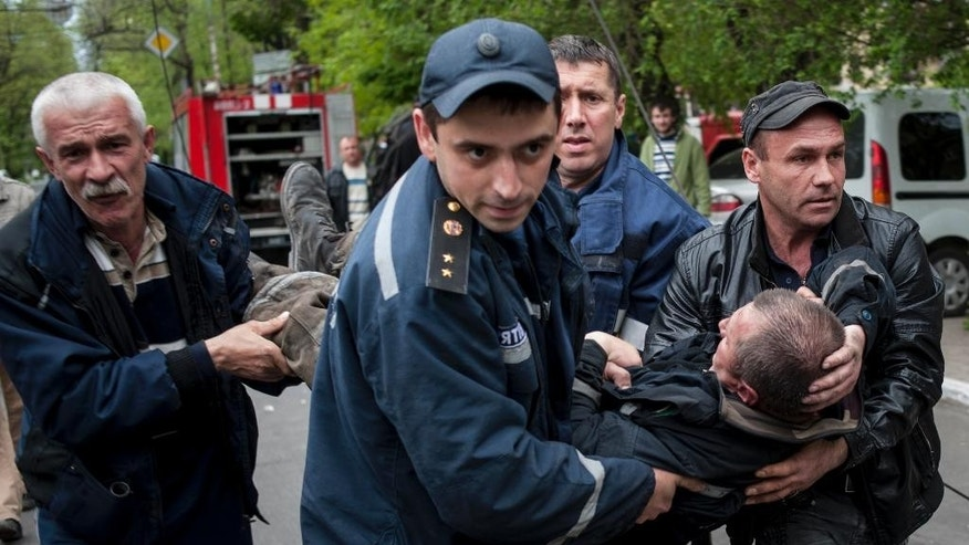 People carry a firefighter injured during an attack at a police station in Mariupol, eastern Ukraine, Friday, May 9, 2014. Fighting between government forces and insurgents in Mariupol has left several people dead. (AP Photo/Evgeniy Maloletka)
