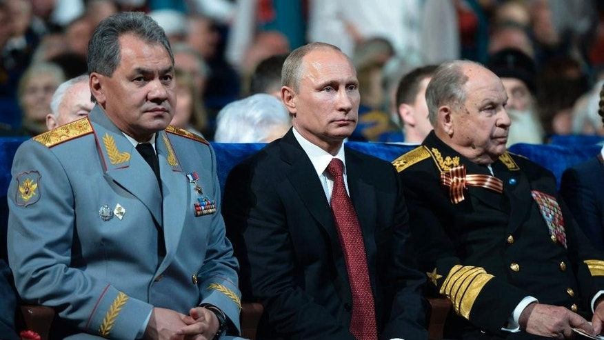 Russian President Vladimir Putin, center, and Defense Minister Sergei Shoigu, left, attend a gala concert on the eve of Victory Day marking the defeat of Nazi Germany 69 years ago, in the Kremlin in Moscow, Russia, Thursday, May 8, 2014. Russia will mark Victory Day on May 9 holding a military parade in Red Square in Moscow. (AP Photo/RIA-Novosti, Alexei Nikolsky, Presidential Press Service)
