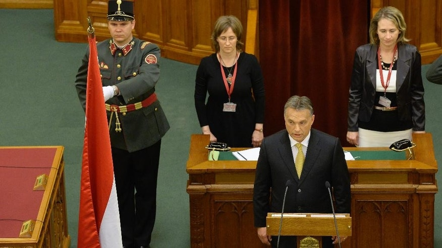 Incumbent Hungarian Prime Minister Viktor Orban, foreground, swears in,  after he was reelected by the majority of MPs during a session of the Parliament in Budapest, Hungary, Saturday, May 10, 2014. Orban's reelection comes after his centre-right Fidesz party won a two third majority in the parliamentary elections last April. (AP Photo/MTI, Lajos Soos)