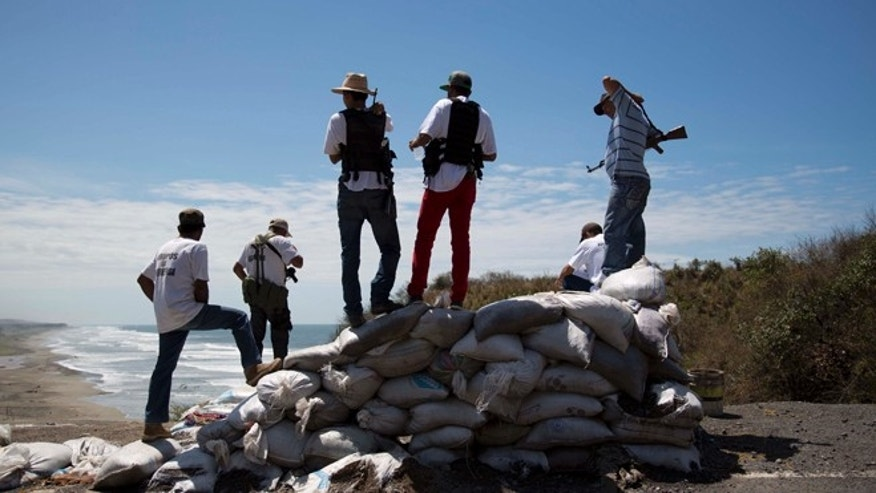 Armed men belonging to the Self-Defense Council of Michoacan (CAM) look out toward the sea as they guard a checkpoint set up by the self-defense group in Chuquiapan on the outskirts of the seaport of Lazaro Cardenas in western Mexico, Friday, May 9, 2014. Mexicos government plans on Saturday to begin demobilizing the vigilante movement that largely expelled the Knights Templar cartel when state and local authorities couldnt. But tension remained on Friday in the coastal part of the state outside the port of Lazaro Cardenas, where some self-defense groups plan to continue as they are, defending their territory without registering their arms. (AP Photo/Eduardo Verdugo)
