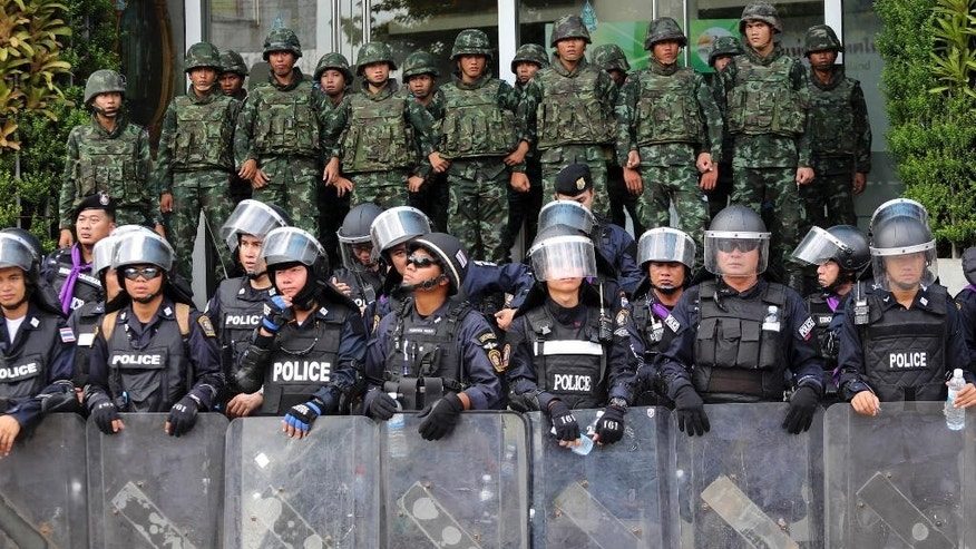 Riot police officers, foreground, and soldiers guard the National Broadcasting of Thailand (NBT) building after anti-government protesters entered the compound during a rally Friday, May 9, 2014 in Bangkok, Thailand. Thai police fired tear gas and water cannons Friday to push back hundreds of protesters trying to force their way into a government compound, the latest indication that ousting the premier will not solve the country's tense political crisis. (AP Photo/Apichart Weerawong)