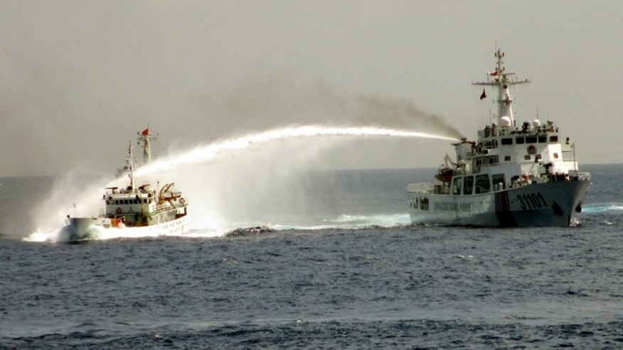May 4, 2014: This image made from video released by Vietnam Coast Guard shows a Chinese coast guard vessel, right, firing water cannon at a Vietnamese vessel off the coast of Vietnam.