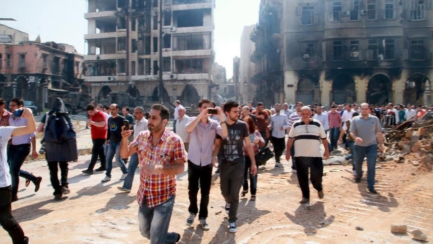 In this photograph made on a government-led media tour, Syrian civilians return to Homs, Syria on Friday, May 9, 2014, where bulldozers cleared rubble from the streets of battle-scarred districts in the central Syrian city after government troops entered the last rebel-held neighborhoods as part of an agreement that also granted opposition fighters safe exit from the city. (AP Photo)