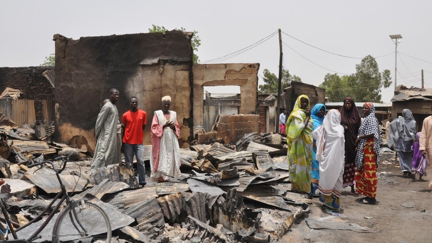 May 11, 2014 - People stand outside burnt houses following an attack by Islamic militants in Gambaru, Nigeria. Many brutalized residents of the once bustling town of Gamboru  say they are moving across the border to Cameroon because they cannot trust the Nigerian government to protect them.