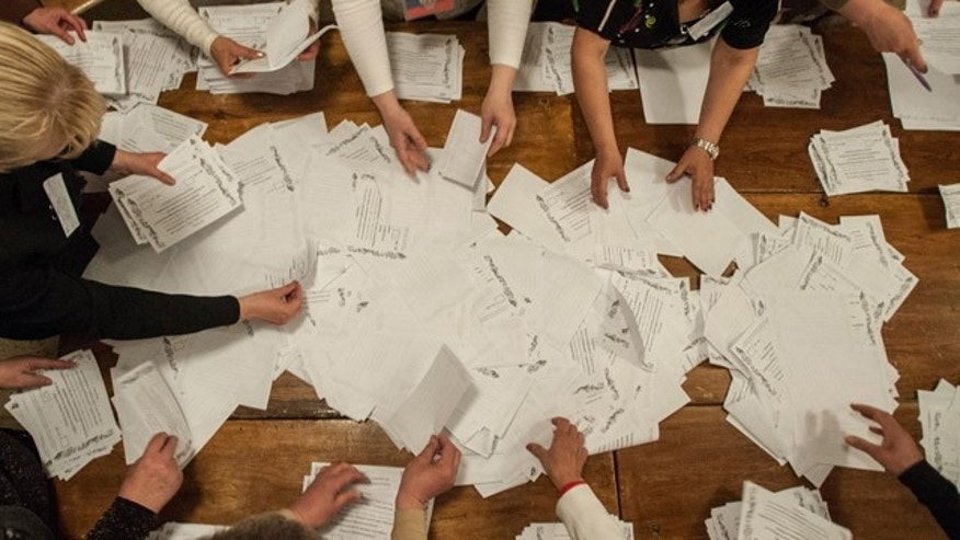 May 11, 2014: Members of an election committee count ballots after voting closed at a polling station in Donetsk, Ukraine. (AP Photo/Evgeniy Maloletka)