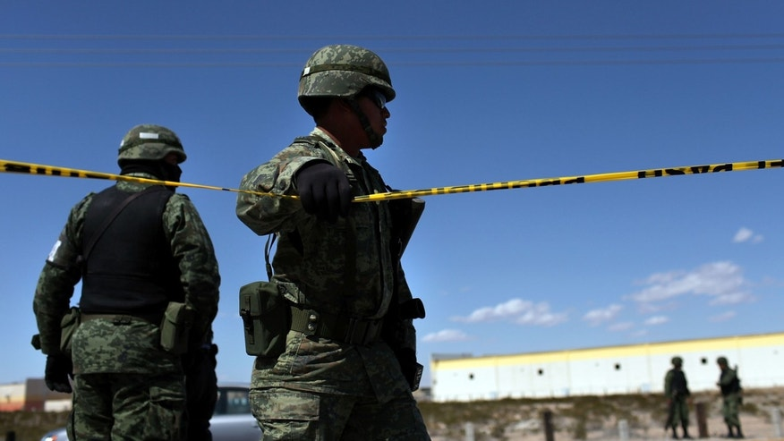 JUAREZ, MEXICO - MARCH 24:  A member of the Mexican military police keeps guard over a car with Texas license plates bearing a bullet-ridden body on March 24, 2010 in Juarez, Mexico. Secretary of State Hillary Rodham Clinton, Defense Secretary Robert Gates, and Homeland Security Secretary Janet Napolitano all visited Mexico yesterday for discussions centered on Mexico's endemic drug-related violence. The border city of Juarez, Mexico has been racked by violent drug-related crime recently and has quickly become one of the most dangerous cities in the world in which to live. As drug cartels have been fighting over ever-lucrative drug corridors along the United States border, the murder rate in Juarez has risen to 173 slayings for every 100,000 residents. President Felipe Calderon's strategy of sending 7000 troops to Juarez has not mitigated the situation. With a population of 1.3 million, 2,600 people died in drug-related violence last year and 500 so far this year, including two Americans recently who worked for the U.S. Consulate and were killed as they returned from a child's party.  (Photo by Spencer Platt/Getty Images)