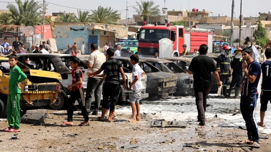 May 13, 2014: Civilians inspect the site of a car bomb explosion in the Shiite stronghold of Sadr City, in Baghdad, Iraq. (AP)