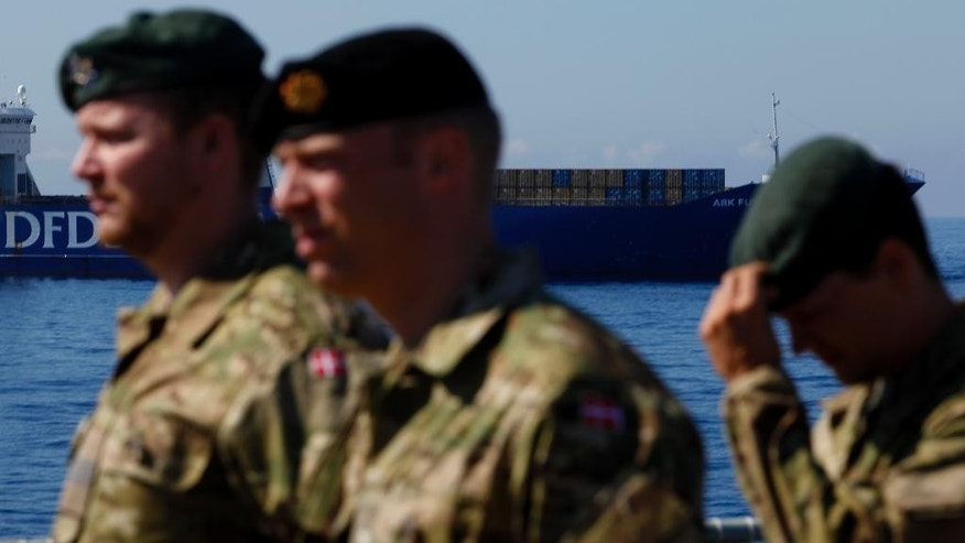 "Danish soldiers are seen onboard the Danish warship ""Esbern Snare"", as in the background the Danish cargo ship Ark Futura carries Syria's dangerous chemical weapons which are being transported out of the strife-torn country, in the coastal city of Larnaca, Cyprus, Tuesday, May 13, 2014. Denmark's foreign minister Martin Lidegaard  is urging Syria to give up the last of its chemical weapons agents in the next few days in order to meet a June 30 deadline for completely ridding the war-torn country of its lethal stockpile. A Danish-Norwegian flotilla consisting of two warships and two cargo vessels has been moving the chemicals out of Syria for eventual destruction since January. (AP Photo/Petros Karadjias)"