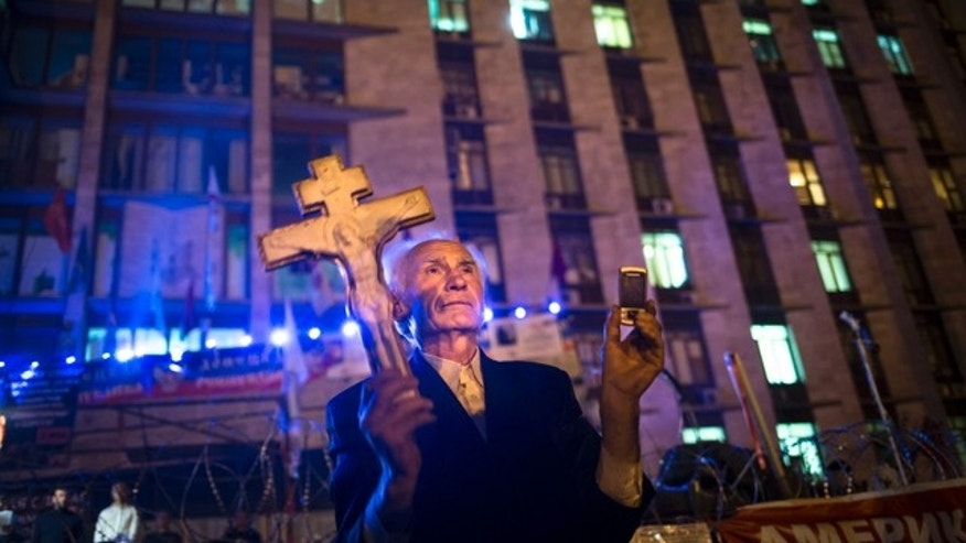 May 12, 2014: A pro-Russian man holds an Orthodox cross as a crowd celebrate declaring independence for Donetsk region at barricades in front of a regional administration building that was seized by pro-Russian activists. (AP Photo/Alexander Zemlianichenko)