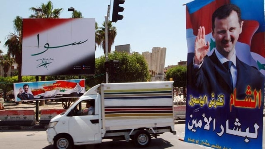 May 12, 2014: A vehicle drives past campaign posters for the June 3 presidential election in Damascus, Syria. (AP Photo)