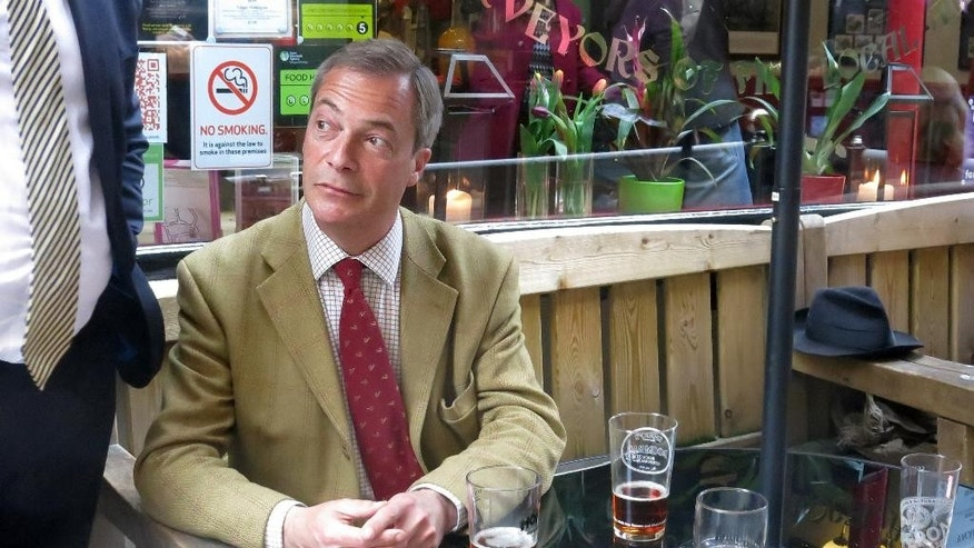 In the Photo taken Tuesday, April  29, 2014, United Kingdom Independence Party leader Nigel Farage sits in a pub in Bath, England, talking to members of the public and media during a campaign stop for the European Elections. Farage, leader of the United Kingdom Independence Party, sips his impeccably English pint of beer with the smile of a man on track to win the biggest share of British votes in elections this month for the European Parliament _ a parliament Farage wants to abolish, along with the entire 28-nation EU bloc.(AP Photo/Jill Lawless)
