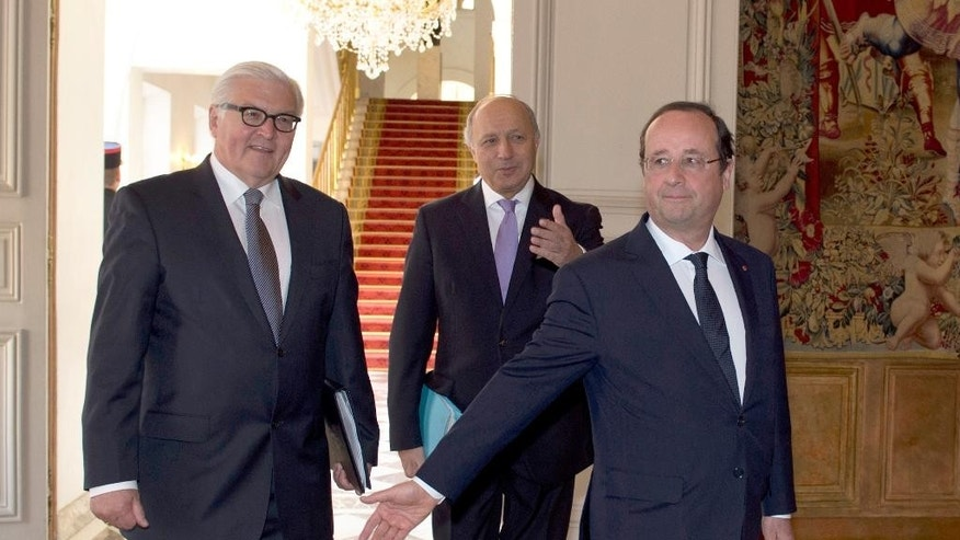 German Foreign Minister Frank-Walter Steinmeier, left,  French President Francois Hollande, right, and French Foreign Minister Laurent Fabius arrive at the weekly cabinet meeting at the Elysee palace, Wednesday May 14, 2014, in Paris.  (AP Photo/Alain Jocard, Pool)