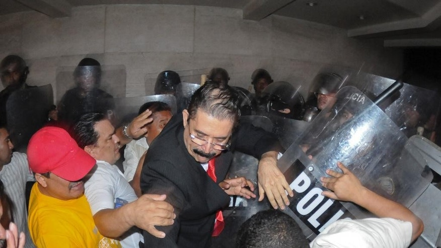 Manuel Zelaya, center, former Honduran President and now congressman, is forcibly expelled by riot police from the congress building along with other members of the Libertad y Refundacion, LIBRE party, in Tegucigalpa, Honduras, Tuesday, May 13 2014. Hundreds of Zelaya's supporters clashed with riot police and soldiers and where eventually expelled violently from the building. (AP Photo/Fernando Antonio)