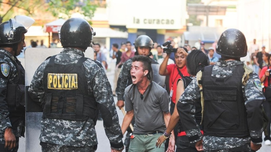 Supporters of the Libertad y Refundacion, LIBRE, political party, shout slogans against the Honduran government during a clashes with police, outside the congress building in Tegucigalpa, Honduras, Tuesday, May 13, 2014. Hundreds of supporters of former President and now Congressman, Manuel Zelaya, clashed with riot police and soldiers after occupying the National Congress building with him. They where eventually expelled violently from the building. (AP Photo/Fernando Antonio)