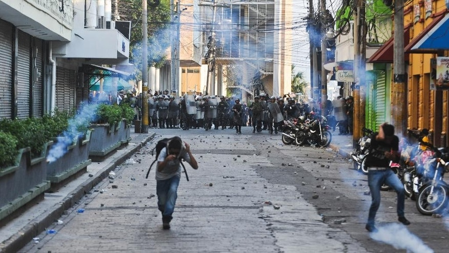Supporters of the Libertad y Refundacion, LIBRE, political party, run away from tear gas grenades as they protest against the Honduran government during a clashes with police, outside the congress building in Tegucigalpa, Honduras, Tuesday, May 13, 2014. Hundreds of supporters of former President and now Congressman, Manuel Zelaya, clashed with riot police and soldiers after occupying the National Congress building with him. They where eventually expelled violently from the building. (AP Photo/Fernando Antonio)