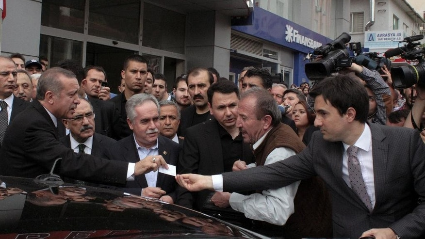 In this Wednesday, May 14, 2014 photo, Yusuf Yerkel, right, advisor to Turkish Prime Minister Recep Tayyip Erdogan, receives a note from Erdogan during his visit in Soma, Turkey. Yerkel  identified by the Turkish media as the advisor who allegedly kicked a protester who was held by special forces police members during Erdogan's visit to Soma. Erdogan was visiting the western Turkish mining town of Soma after Turkey's worst mining accident.(AP Photo/Depo Photos) TURKEY OUT  ONLINE OUT