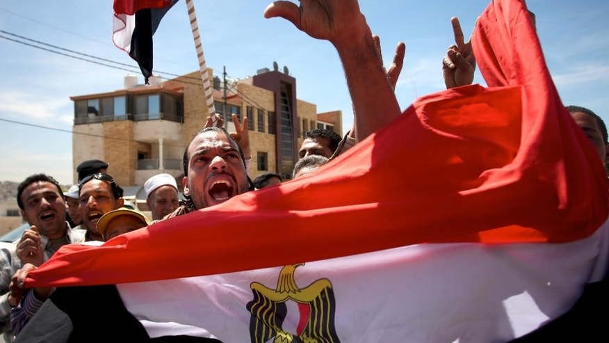 Egyptians hold national flags and chant slogans outside the Egyptian embassy in Amman, Jordan, Thursday, May 15, 2014. Egyptian expatriates around the world headed to the polls on Thursday, casting the first votes to name a successor to deposed Islamist President Mohammed Morsi. (AP Photo/Mohammad Hannon)