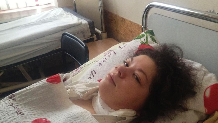 """FILE - In this Feb. 21, 2014 file photo, Olesya Zhukovska lies on her hospital bed in Kiev, Ukraine, after being hit by a sniper's bullet. The scars are fading now. The exit wound, a narrow, pink line that curves down the left side of her neck, is often hidden by her tangle of dark hair. And Zhukovska, who became a symbol of Ukraine's protests when she tweeted """"I am dying"""" after the bullet tore into her on that cold February morning, sometimes wonders just what it all achieved. (AP Photo/Maria Danilova, File)"""