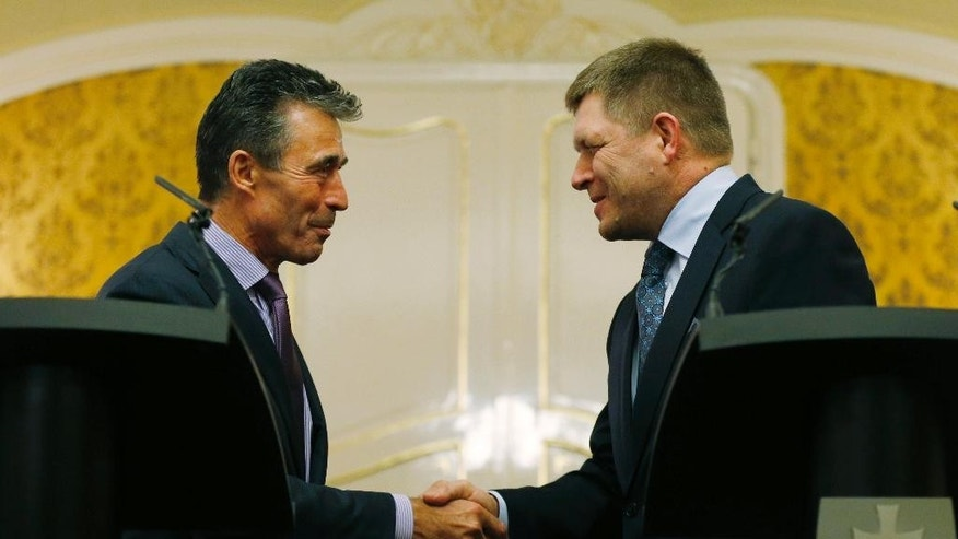 NATO Secretary General Anders Fogh Rasmussen, left, shake hands with Slovakia's Prime Minister Robert Fico as they meet in Bratislava, Slovakia, Thursday, May 15, 2014. (AP Photo/Petr David Josek)