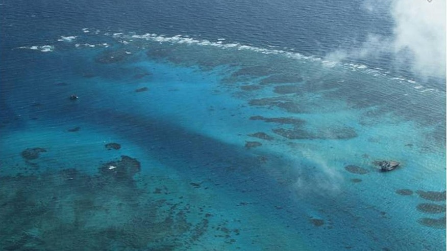 In this photo taken March 13, 2012 by surveillance planes and released Thursday, May 15, 2014, by the Philippine Department of Foreign Affairs,  the Johnson Reef, locally called Mabini Reef, called Mabini by the Philippines and Chigua by China, is seen at the Spratly Islands at South China Sea. The Philippines has protested China's reclamation of land in the disputed reef in the South China Sea that can be used to build an airstrip or an offshore military base in the increasingly volatile region, the country's top diplomat and other officials said. The white arrow, top right, was added by the source. (AP Photo/Philippine Department of Foreign Affairs)
