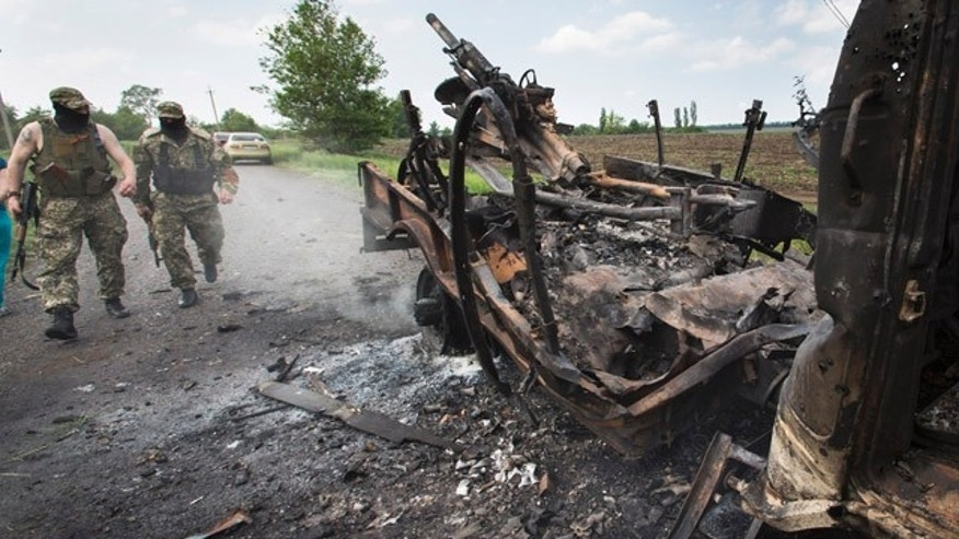 May 14, 2014: Two armed pro-Russians walk towards a seized military track with a mortar atop that was set alight during fighting between pro-Russian militants and government troops at Oktyabrskoye village, about 12 miles from Kramatorsk in eastern Ukraine. (AP Photo/Alexander Zemlianichenko)