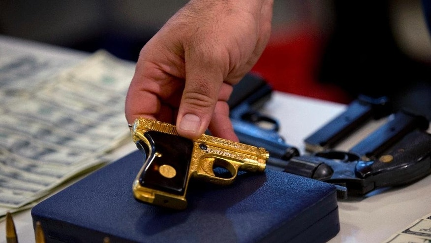 Argentina's Security Secretary Sergio Berni holds a pistol that was part of a cache seized during an anti-drug raid, during a media presentation in Buenos Aires, Argentina, Friday, May 16, 2014. The Argentine government on Friday announced the dismantling of a band of transnational drug traffickers who transported liquid cocaine from Argentina to Mexico with the intention of diverting to Europe and the United States. Weapons, computers and banknotes that were seized in the anti-drug operation were presented at the press conference. (AP Photo/Natacha Pisarenko)