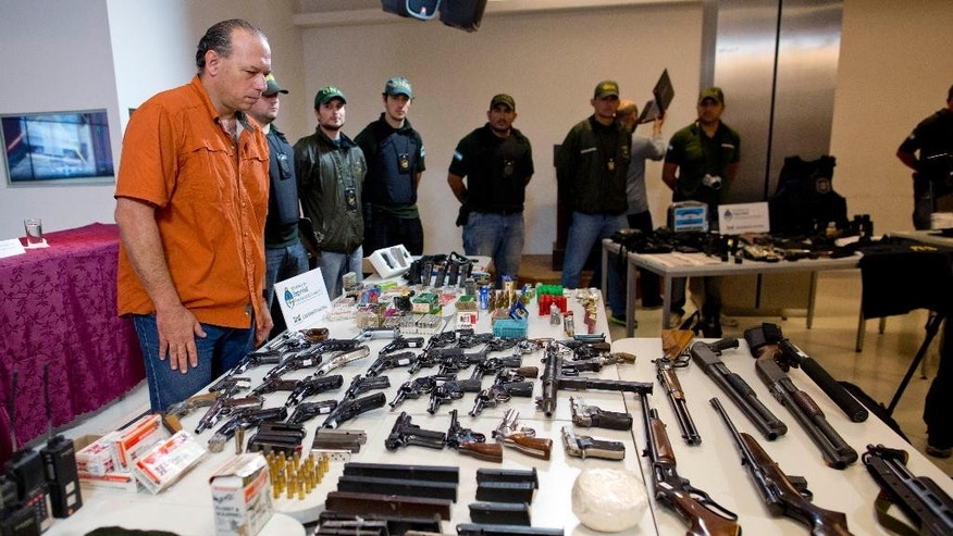 Argentina's Security Secretary Sergio Berni stands before a table displayed with weapons that were seized during an anti-drug raid, at a media presentation in Buenos Aires, Argentina, Friday, May 16, 2014. The Argentine government on Friday announced the dismantling of a band of transnational drug traffickers who transported liquid cocaine from Argentina to Mexico with the intention of diverting to Europe and the United States. Weapons, computers and banknotes that were seized in the anti-drug operation were presented during a press conference. (AP Photo/Natacha Pisarenko)