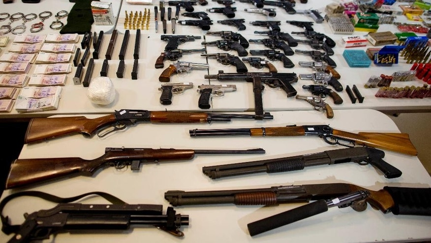 Weapons that were seized during an anti-drug raid, are displayed on a table for a media presentation in Buenos Aires, Argentina, Friday, May 16, 2014. The Argentine government on Friday announced the dismantling of a band of transnational drug traffickers who transported liquid cocaine from Argentina to Mexico with the intention of diverting to Europe and the United States. Weapons, computers and banknotes that were seized in the anti-drug operation were presented during a press conference. (AP Photo/Natacha Pisarenko)