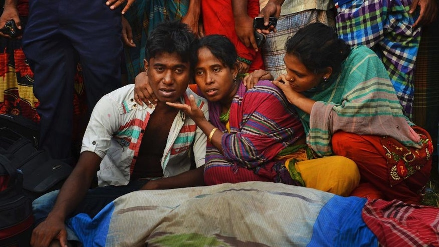 Unidentified Bangladeshi relatives wail near bodies of victims on the banks of the River Meghna after a ferry carrying more than 100 passengers capsized and sank after being hit by a storm in Munshiganj district, Bangladesh, Thursday, May 15, 2014. According to an official eight bodies have been recovered and there was confusion about the number of missing people. (AP Photo/Sony Ramany)