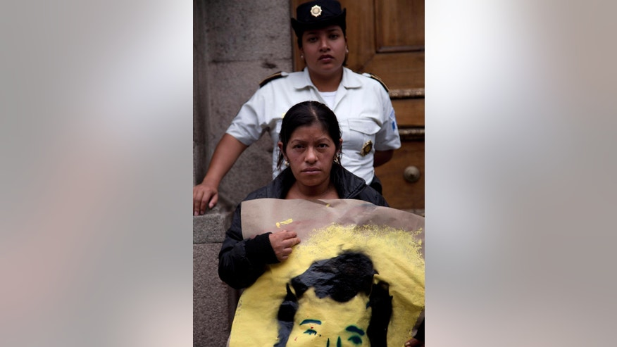 "A police agent stands guard at the National Congress, as a demonstrator holds a portrait of a person disappeared in the 80's during a protest against a resolution that denies there was any attempt to commit genocide during the bloody 36-year civil war, in Guatemala City, Friday, May 16, 2014. ""It is legally impossible ... that genocide could have occurred in our country's territory during the armed conflict,"" said the resolution, which passed late Tuesday, May 13, 2014, with support from 87 of the 158 legislators. (AP Photo/Moises Castillo)"