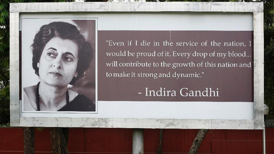In this Saturday, May 10, 2014 photo, an Indian man sleeps on a bench below a billboard displaying a portrait and quote of former Indian Prime Minister Indira Gandhi in New Delhi, India. In an election campaign led by Rahul Gandhi - the son, grandson, and great-grandson of Indian prime ministers - the Indian National Congress party suffered the most crushing defeat in its 128-year history Friday when the results of India's general election were released. (AP Photo/Altaf Qadri)
