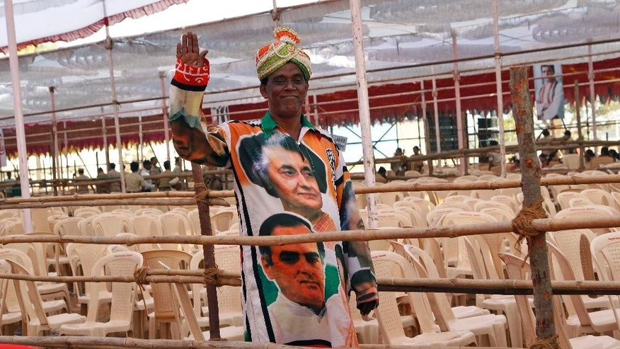 FILE - In this Thursday, March 6, 2014 file photo, a supporter of India's Congress party wearing an outfit with portraits of former Indian Prime Ministers Indira Gandhi, top, and Rajiv Gandhi, waves to camera at an election campaign rally addressed by the party vice president and scion of the Nehru-Gandhi family Rahul Gandhi in Thane, on the outskirts of Mumbai, India. In an election campaign led by Rahul Gandhi - the son, grandson, and great-grandson of Indian prime ministers - the Indian National Congress party suffered the most crushing defeat in its 128-year history Friday when the results of India's general election were released. (AP Photo/Rajanish Kakade, File)