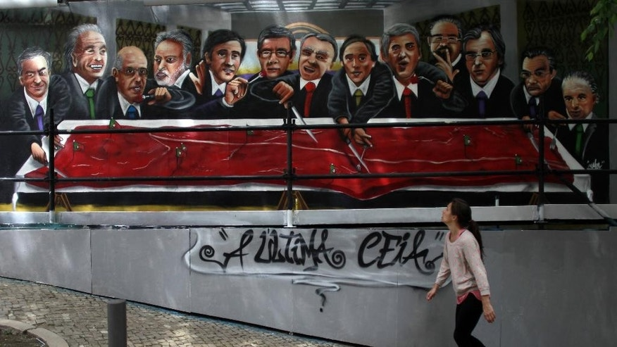 "In this photo taken on April 22, 2014, a woman looks at a graffiti depicting Portugal's Prime Minister Pedro Passos Coelho, fifth left, among other Portuguese politicians and tycoons eating a piece of meat in the shape of the country, in Lisbon. A thousand days on from its near-economic collapse, Portugal is ready to stand on its own again. On Saturday, May 17, 2014,  after an internationally-mandated makeover, Portugal will become the second euro country, after Ireland, to officially shake off its bailout shackles. The sentence under the graffiti reads in Portuguese: ""The Last Supper"". (AP Photo/Francisco Seco)"
