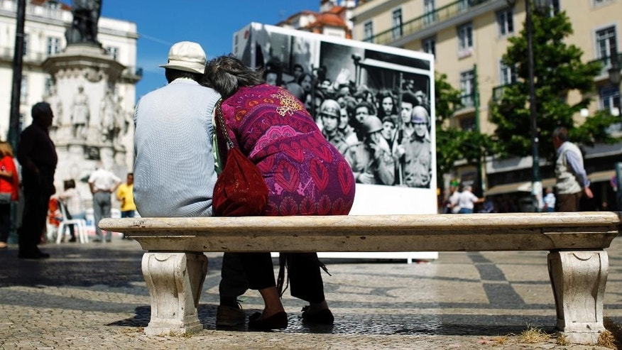 In this photo taken on May 14, 2014, Leoncio Sousa, 76, left, and his wife Cecilia Sousa, 71, sit in a bench before taking part in a protest against pension cuts, in Lisbon. Leoncio, who worked during 42 years as engineer at Lisbon's subway, said that his pension has been cut by 45 percent early 2014. A thousand days on from its near-economic collapse, Portugal is ready to stand on its own again. On Saturday, May 17, 2014,  after an internationally-mandated makeover, Portugal will become the second euro country, after Ireland, to officially shake off its bailout shackles. (AP Photo/Francisco Seco)