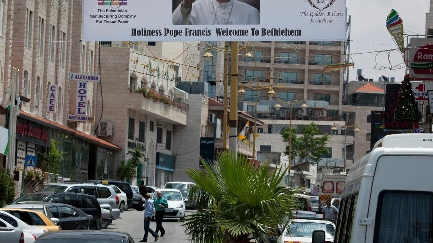 In this Monday, May 12, 2014 photo, a welcome banner with a picture of Pope Francis hangs over a street near the Church of the Nativity, one of the stops of Pope Francis during his upcoming visit in the Holy Land at the end of this month, in the West Bank city of Bethlehem. Israel's internal security agency said it fears there could be more anti-Christian vandalism attacks, and local Vatican officials have urged Israel to safeguard Christian holy sites ahead of the Pope Francis' visit at the end of the month. (AP Photo/Nasser Nasser)