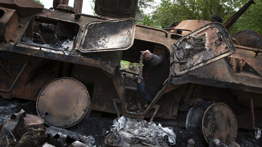 May 14, 2014: A local citizen holds a machine-gun belt as others collect parts of a seized APC that was set alight during a fighting between pro-Russian militants and government troops at Oktyabrskoye village, about 12 miles from Kramatorsk, eastern Ukraine. (AP Photo/Alexander Zemlianichenko)