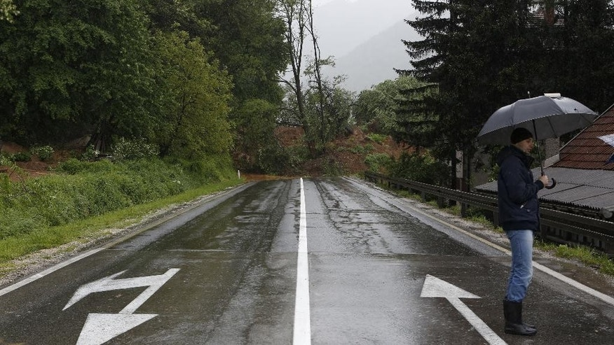 Bosnian man stands near a landslide which blocked a main road in Bosnia in the village of Nemila, 70 kms north of Sarajevo, Thursday May 15, 2014. Heavy rainfall caused the river Bosna to flood surrounding areas causing power cuts and road blockades in some suburban and rural areas. (AP Photo/Amel Emric)