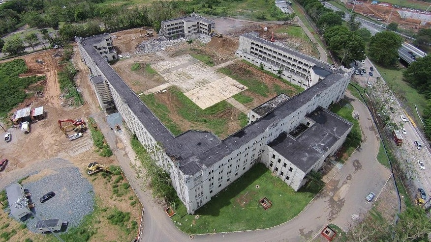 "This May 14, 2014 photo shows an aerial view of demolition work at the former Rio Piedras State Penitentiary, popularly known as the ""Oso Blanco"" in San Juan, Puerto Rico. The Puerto Rican government, which struggled for decades to gain control of the prison known as the ""Alcatraz of the Caribbean,"" wants to demolish most of the structure and build an office park aimed at attracting high-tech businesses. (AP Photo/Ricardo Arduengo)"
