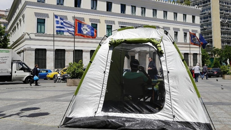 A member of the political party To Potami (The River) uses a tent as an election kiosk outside Athens City Hall in Athens on Thursday, May 17, 2014. To Potami was founded last February by a Greek popular TV journalist Stavros Theodorakis. The first round of municipal and local government elections will be held on Sunday. Greeks will vote in local run-offs on May 25 along with EU Parliament elections. Governing partner New Democracy and main opposition Radical Left Coalition, also known by its acronym, SYRIZA, are vying for first place. (AP Photo/Thanassis Stavrakis)