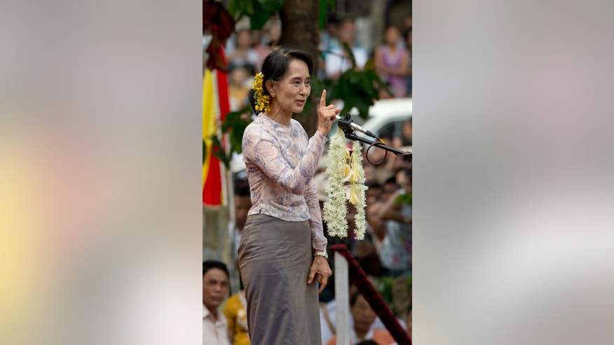 Myanmar opposition leader Aung San Suu Kyi gestures while speaking during a public rally in Yangon, Myanmar, Saturday, May 17, 2014. Democracy activists joined Suu Kyi for the first time calling for an amendment to Myanmar's constitution, a move she says is necessary if next year's general elections are to be free and fair. (AP Photo/Gemunu Amarasinghe)