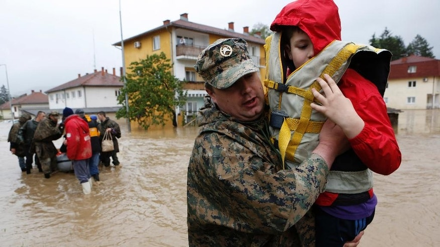 A member of the Bosnian army carries a boy rescued from his home, during floods,   in the Bosnian town of Maglaj, 150 kms north of Sarajevo, Friday May 16, 2014. Two people drowned in Serbia and the country declared a national emergency Thursday as rain-swollen rivers across the Balkans flooded roads and bridges, shut down schools and cut off power. Hundreds of people had to be evacuated. In Serbia and neighboring Bosnia, meteorologists said the rainfall was the most since measuring started 120 years ago. Belgrade authorities say the average rainfall of a two-month period hit the city in just 40 hours. (AP Photo/Amel Emric)