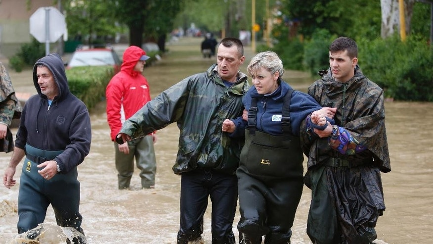 Members of the Bosnian army rescue a woman stranded in her home due to flooding,  in the Bosnian town of Maglaj, 150 kms north of Sarajevo, Friday May 16, 2014. Two people drowned in Serbia and the country declared a national emergency Thursday as rain-swollen rivers across the Balkans flooded roads and bridges, shut down schools and cut off power. Hundreds of people had to be evacuated. In Serbia and neighboring Bosnia, meteorologists said the rainfall was the most since measuring started 120 years ago. Belgrade authorities say the average rainfall of a two-month period hit the city in just 40 hours. (AP Photo/Amel Emric)