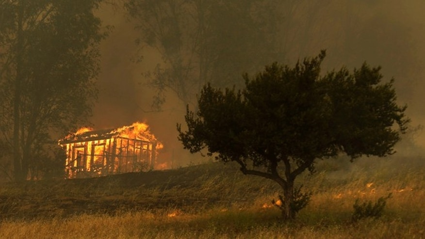 Fire engulfs a structure during a wildfire Thursday, May 15, 2014, in Escondido, Calif. One of the nine fires burning in San Diego County suddenly flared Thursday afternoon and burned close to homes, trigging thousands of new evacuation orders. (AP Photo/Gregory Bull)