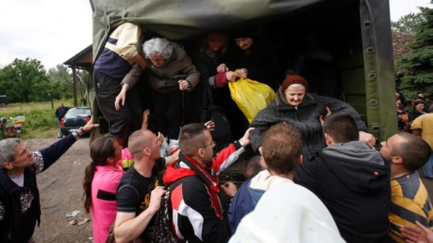 May 17, 2014: People help old women out of a military truck during evacuation from Obrenovac, some 18 miles southwest of Belgrade Serbia.