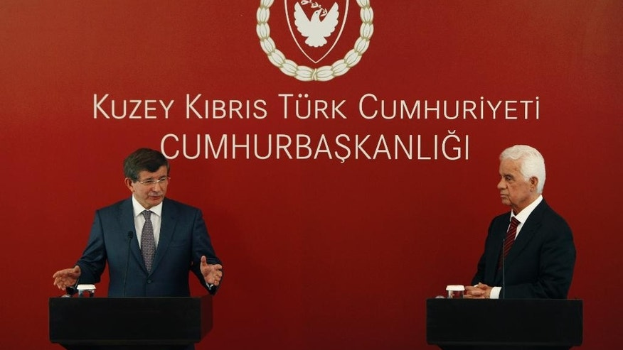 Turkey's Foreign Minister Ahmet Davutoglu, left, speaks to reporters during a press conference after talks with Turkish Cypriot leader Dervis Eroglu, right, after their meeting in the breakaway Turkish Cypriot north of ethnically split Cyprus on Saturday, May 17, 2014. Davutoglu's meeting with Eroglu comes days ahead of a visit to Cyprus by U.S. Vice President Joe Biden amid a new round of talks to reunify the country. (AP Photo/Petros Karadjias)